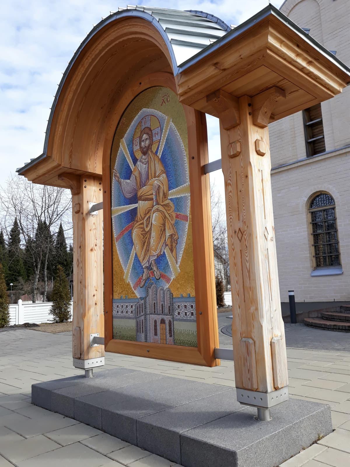 Mosaiikki-ikoni seisoo Puuartistin tekemän puisen holvikaarikatoksen suojissa ortodoksisen seminaarin edessä.