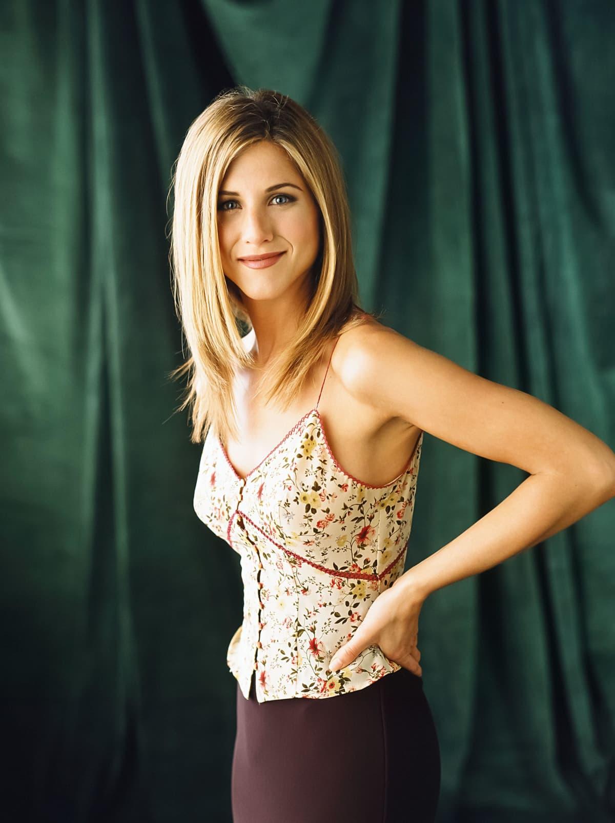 Jennifer Aniston poseeraa kameralle roolihahmonsa Rachel Greenin vaatteissa vihreää kangasta vasten.