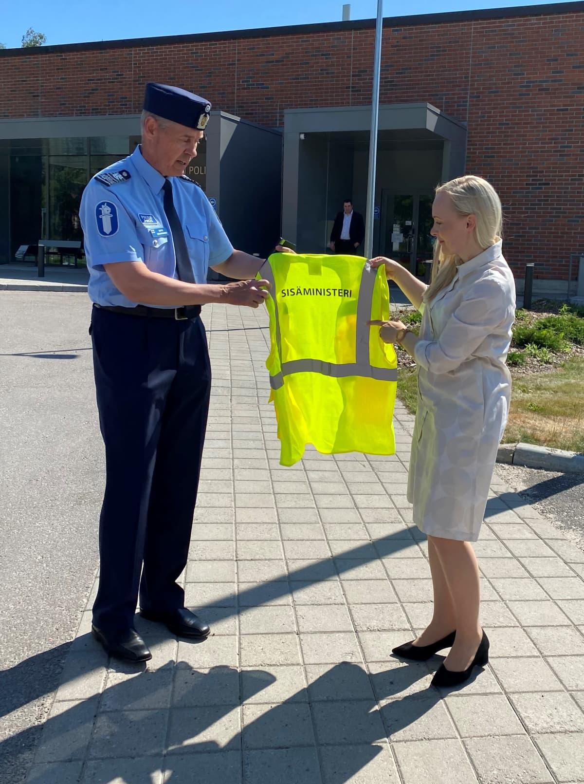 Sisäministeri Maria Ohisalo pitelemässä poliisin avulla turvaliiviä, jossa lukee sisäministeri.