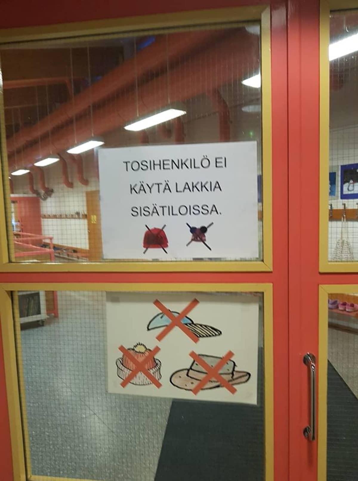 Tosihenkilö ei käytä lakkia sisätiloissa sanotaan koulun kyltissä.