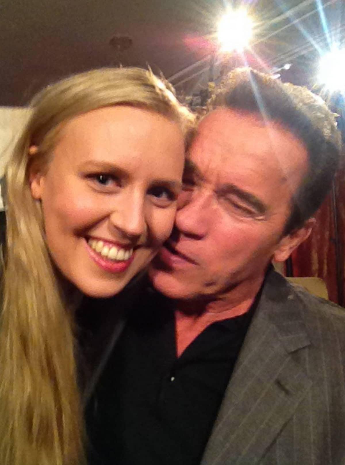 Ylen toimittaja saamassa poskisuudelmaa Arnold Schwarzeneggeriltä.