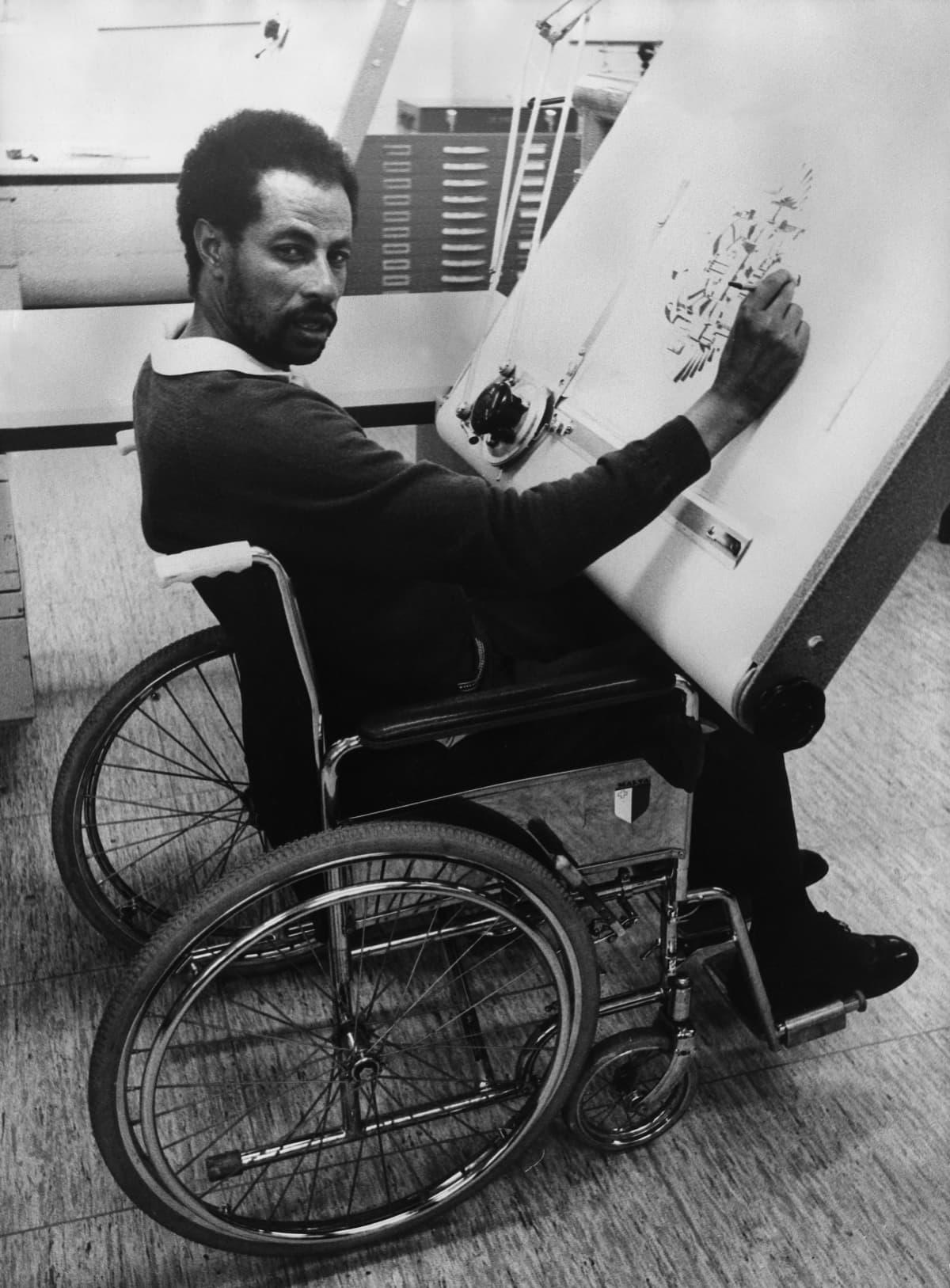 Abebe Bikila, juoksija pyörätuolissa piirustuspöydän ääressä