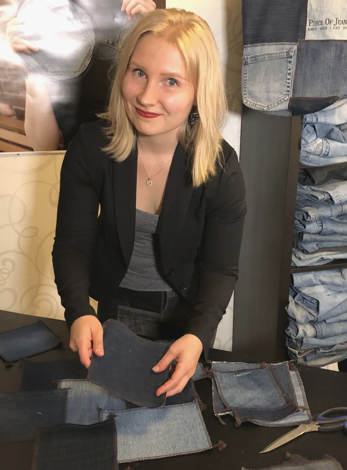 Vaaleahiuksinen nainen hymyilee kuvaajalle työhuoneessa.
