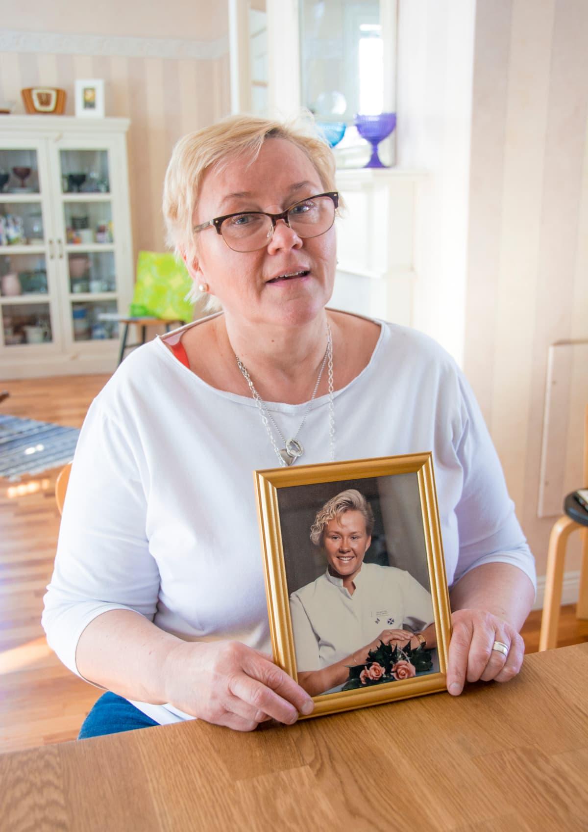 Kuvassa Tarja Kovalainen, joka pitelee käsissään kätilöopiston valmistujaiskuvaansa.