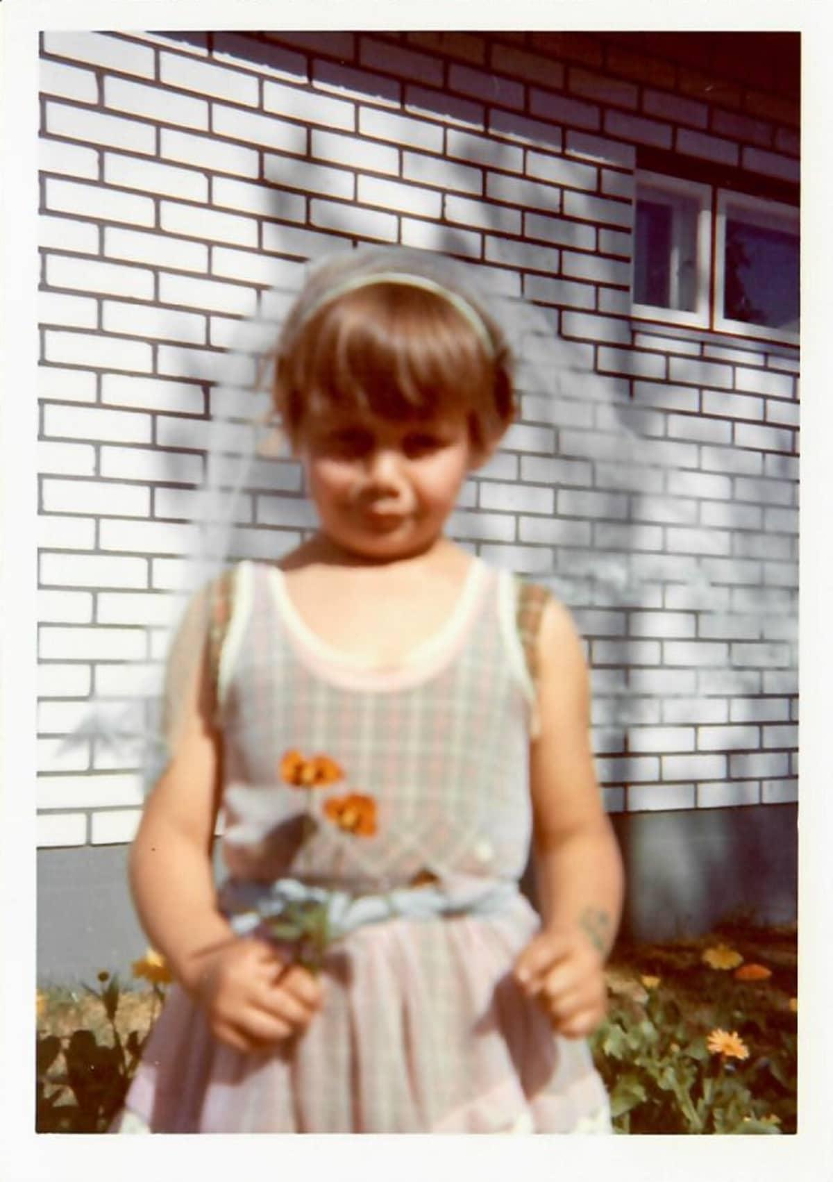 Koskikara lapsena huntu päässä ja kukkia kädessä