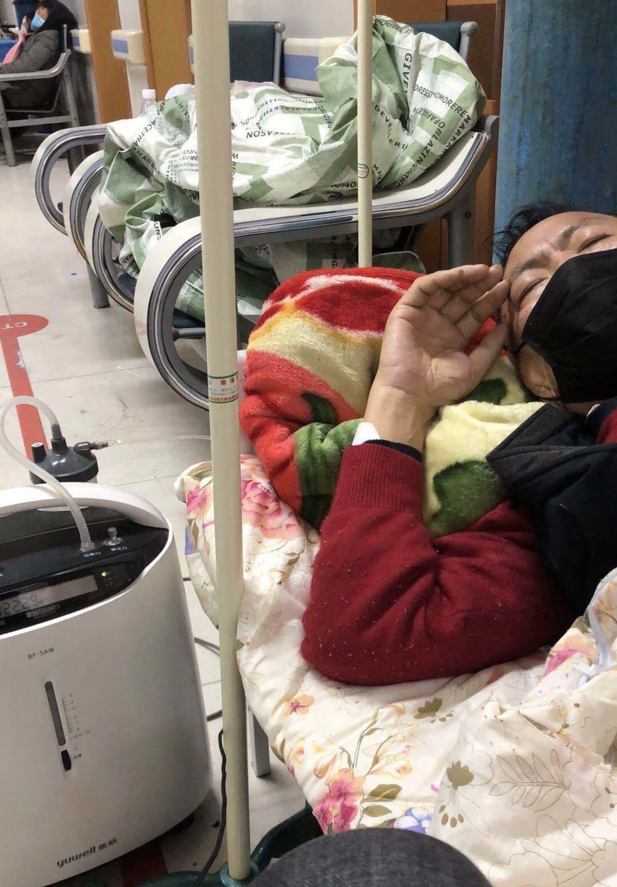 kiinalainen Liguo yang makaa sängyssä kuumeisena hengityssuojain kasvoillaan