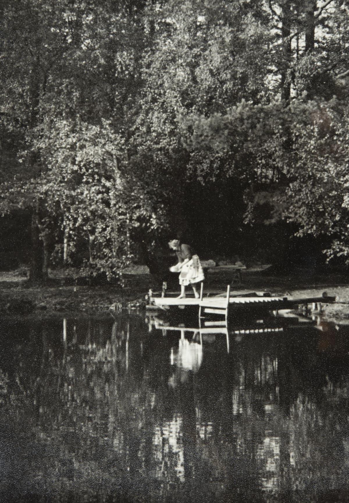 Nainen pyykkaa Kruunuvuorenlammella 1900-luvun puolessavälissä.