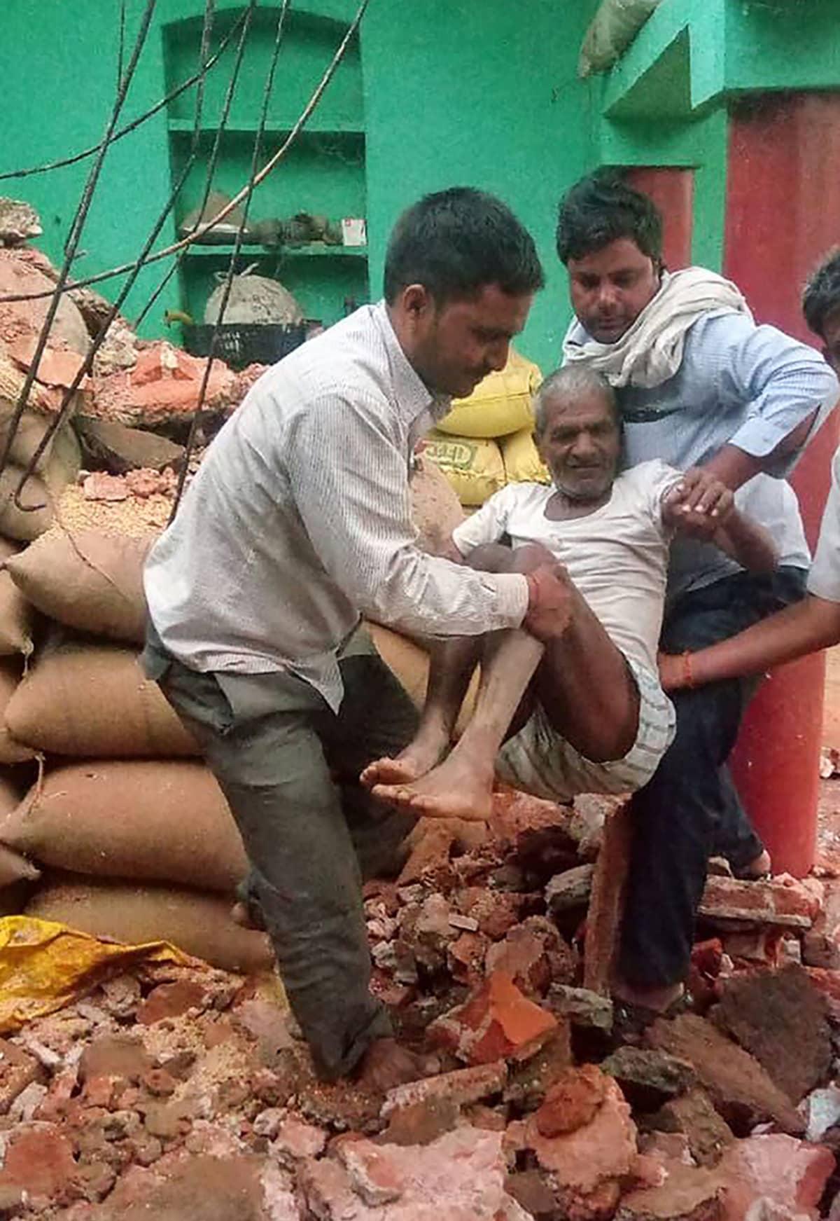 Pelastajat siirtävät miehen vahingoittuneesta talosta Uttar Pradeshin osavaltiossa.