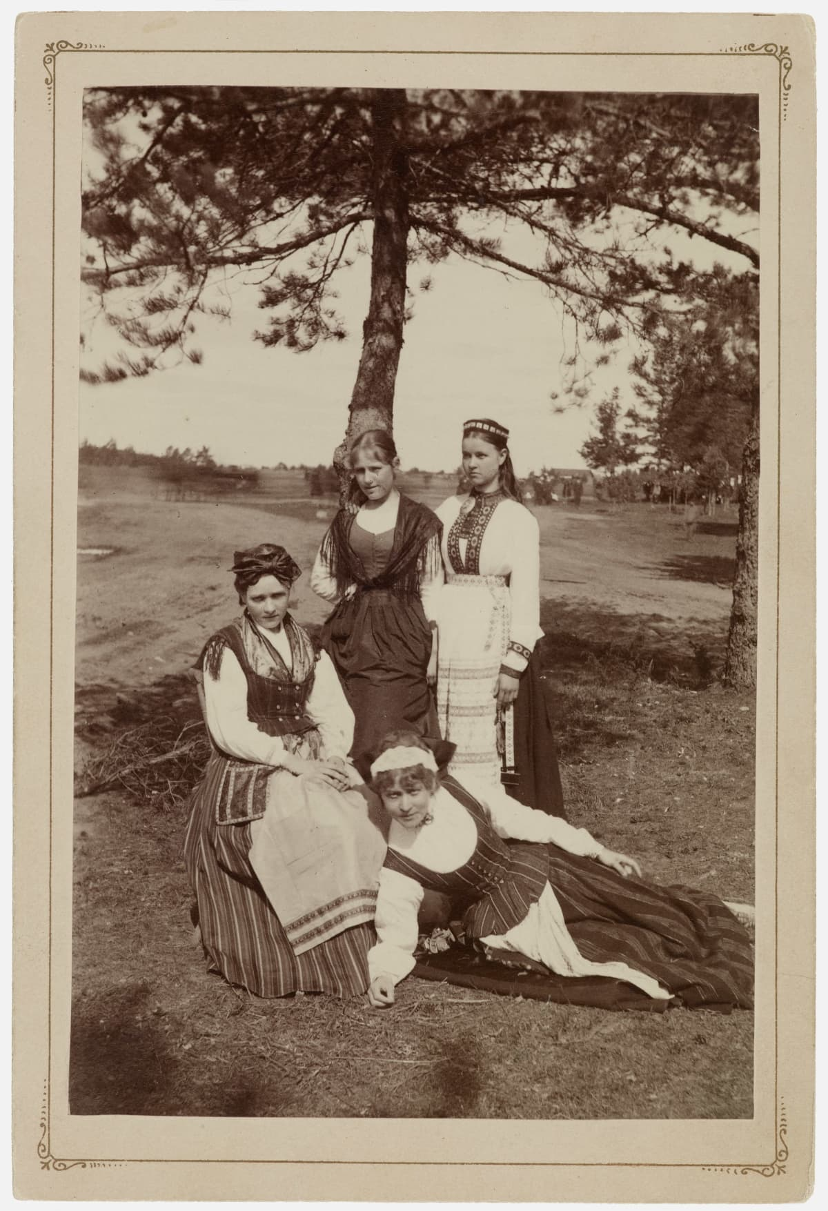 Kesäisessä mustavalkokuvassa kaksi naista seisoo, yksi istuu ja yksi, Ida Aalberg, on makuullaan.