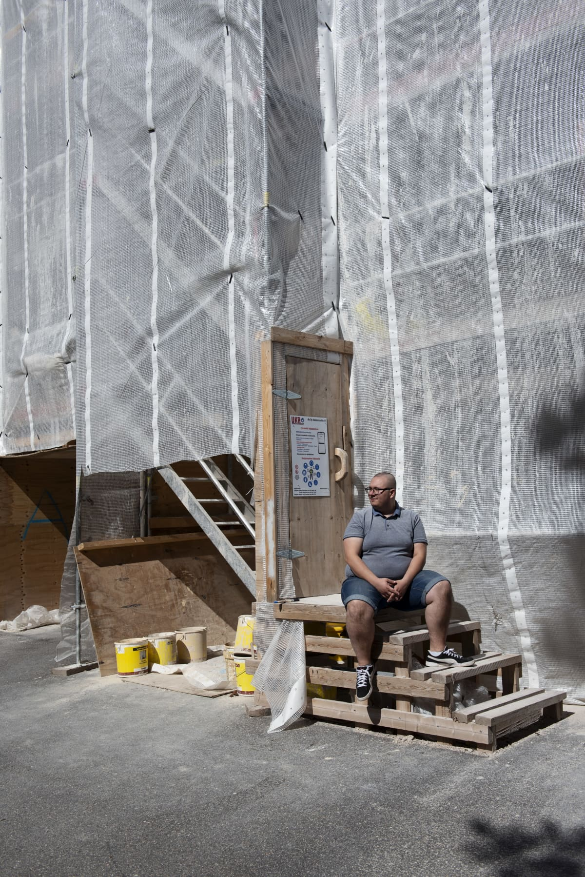 Benjamin Molini huputetun kotinsa edessä Haagassa, työmaan portailla. Talossa on käynnissä iso julkisivuremontti. enjamin Molini kotonaan Haagassa. Asunnon ikkunoista ei näy ulos eikä niitä saa auki, sillä talossa on käynnissä suuri julkisivuremontti.