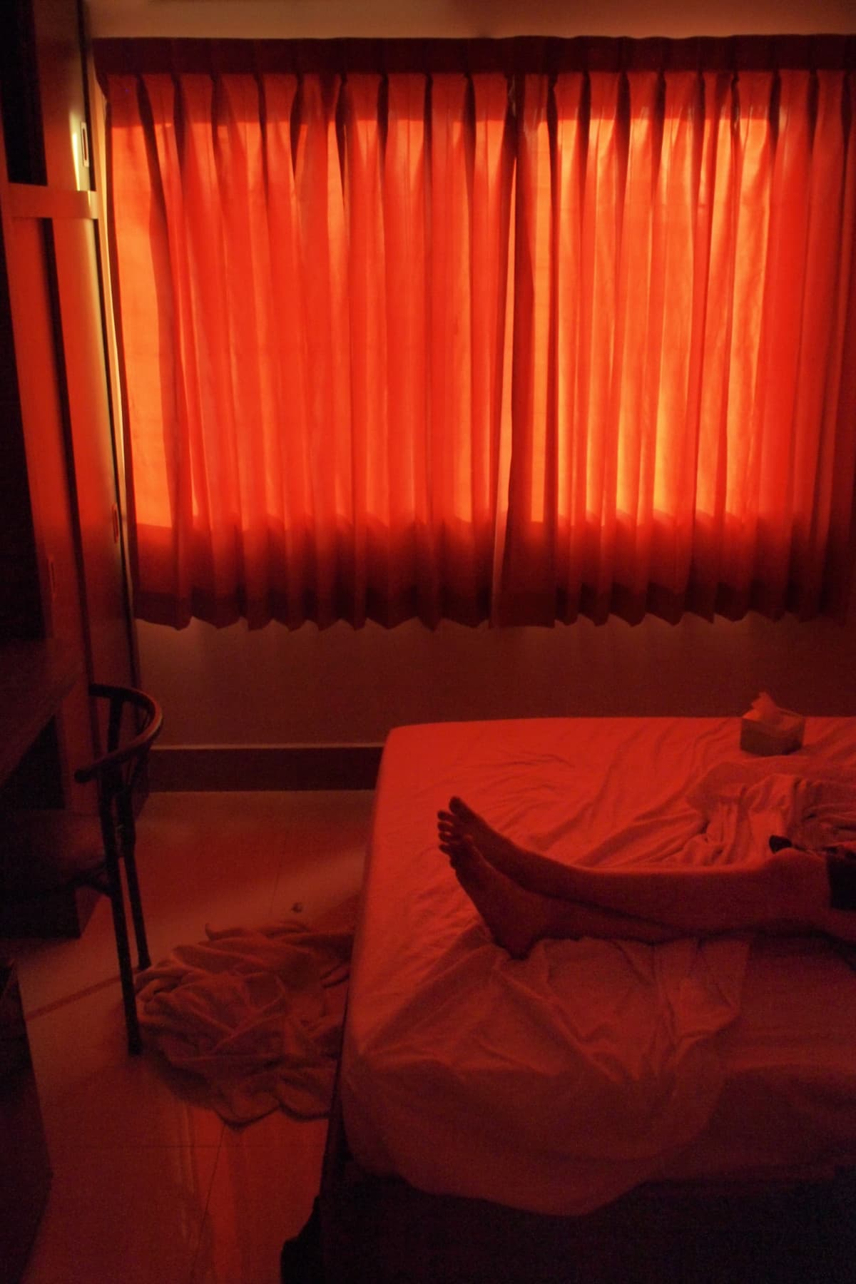 Jalat sängyllä punaiseksi värjäytyneessä huoneessa