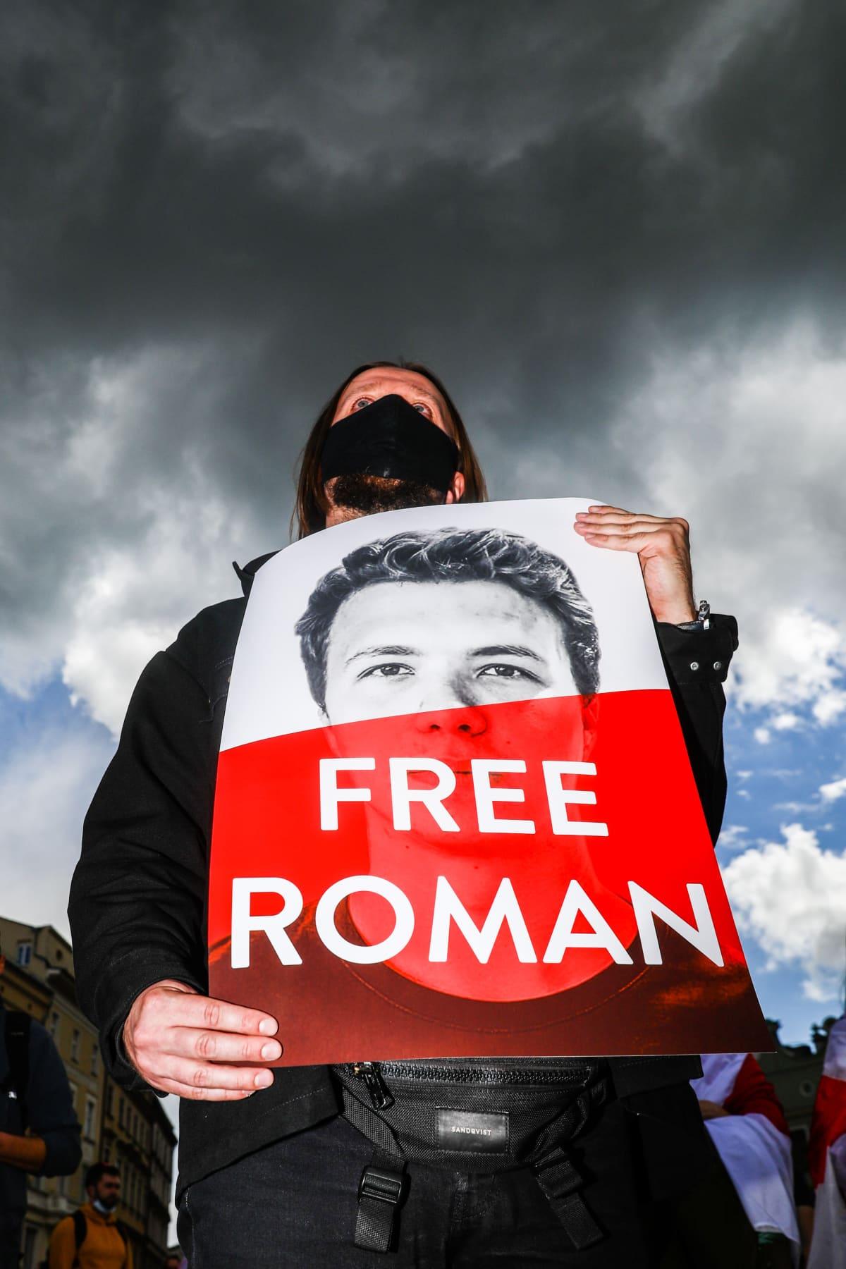 Mies pitää Free Roman kylttiä edessään mielenosoituksessa.