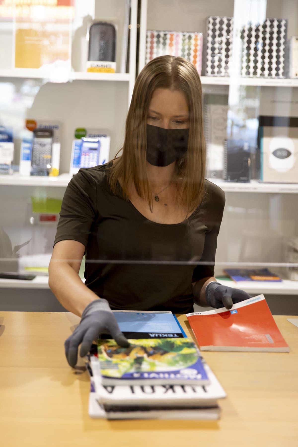 Myyjä Tuula Tarkkonen tarkastaa käytettyjen lukiokirjojen kuntoa Jamera Oy:n myymälässä.