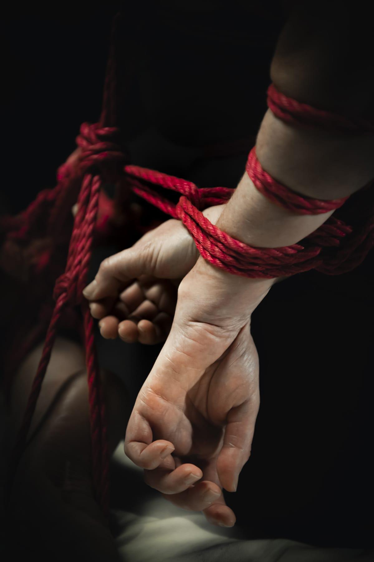 Naisen kädet sidottuna.