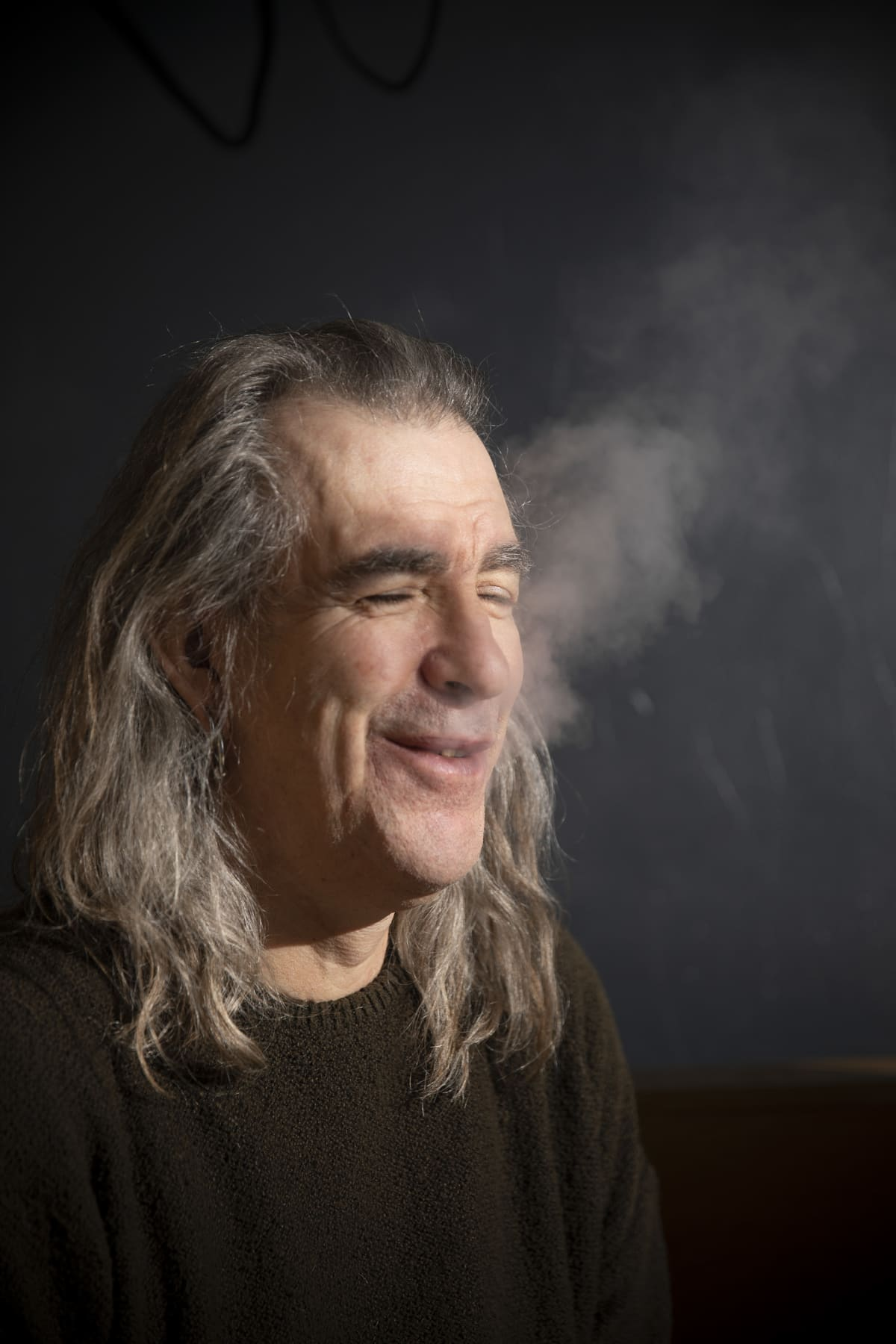 Justin Sullivan puhaltaa savua ja hymyilee