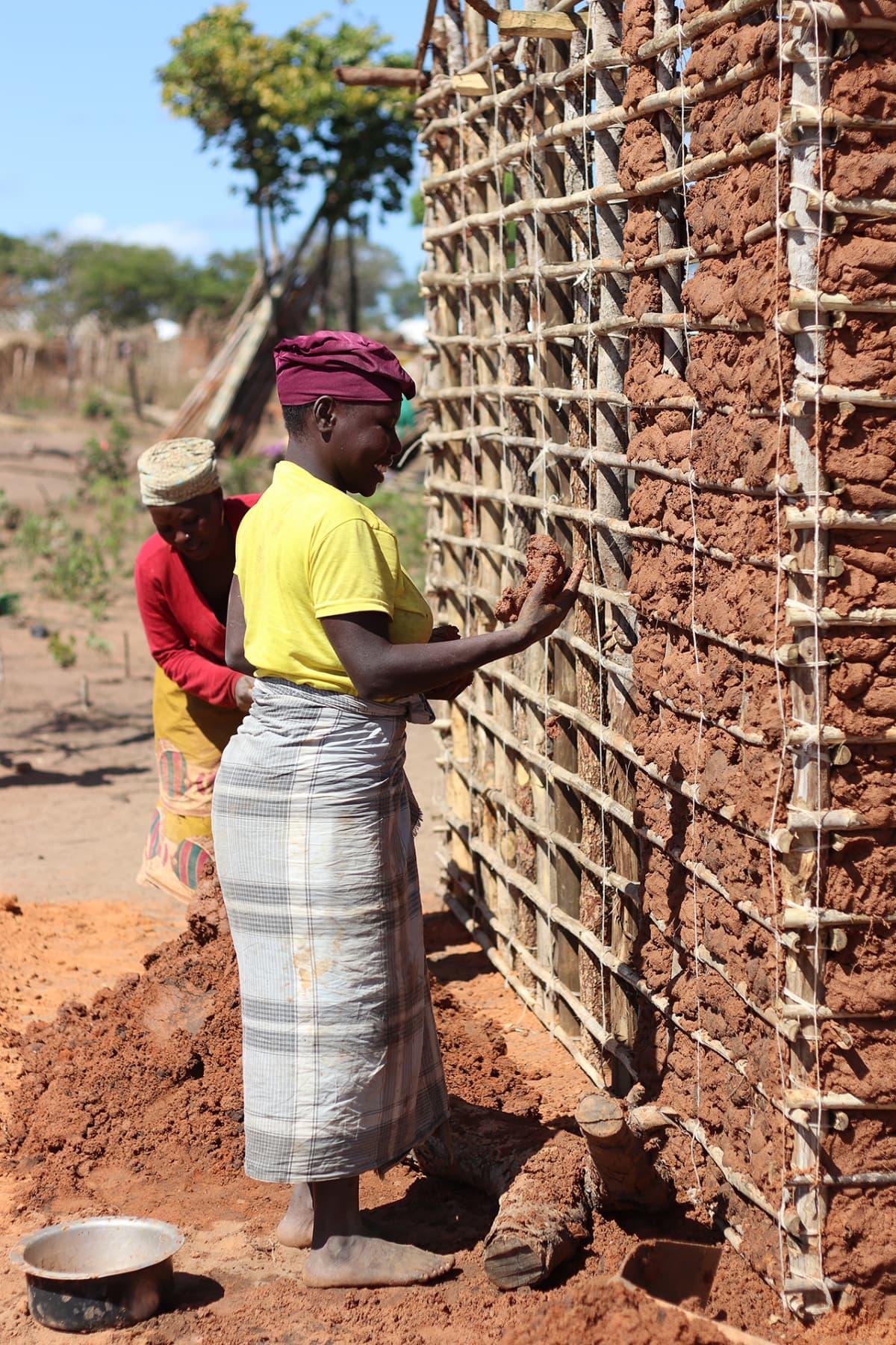 Nainen tiivistää uuden majansa seiniä punaisella hiekkaseoksella. Suuri osa pakolaisista rakentaa uutta elämää kaukana kotoaan.