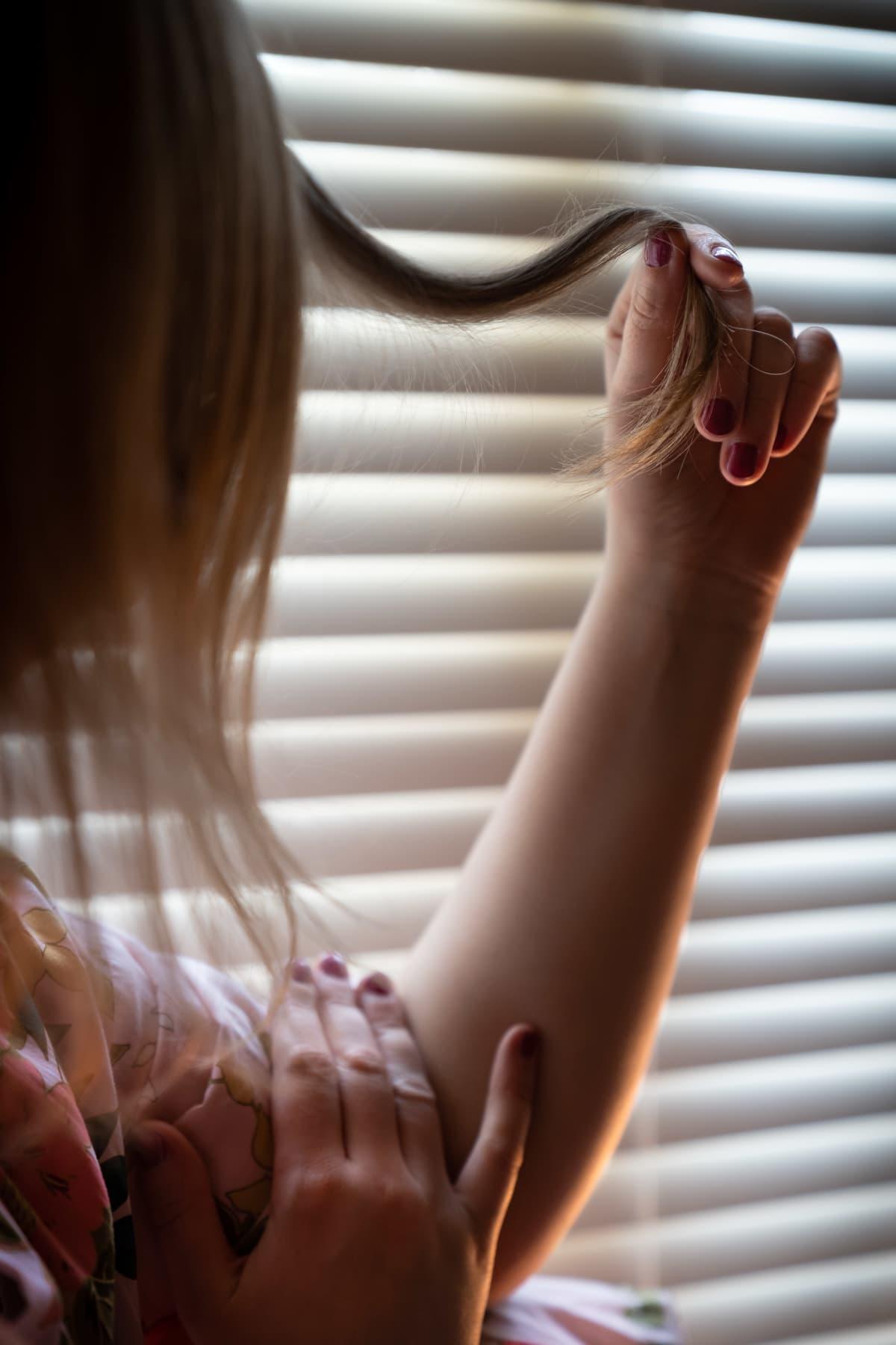 Anonyymi nainen ikkunan ääressä pyörittelee hiussuortuvaa.