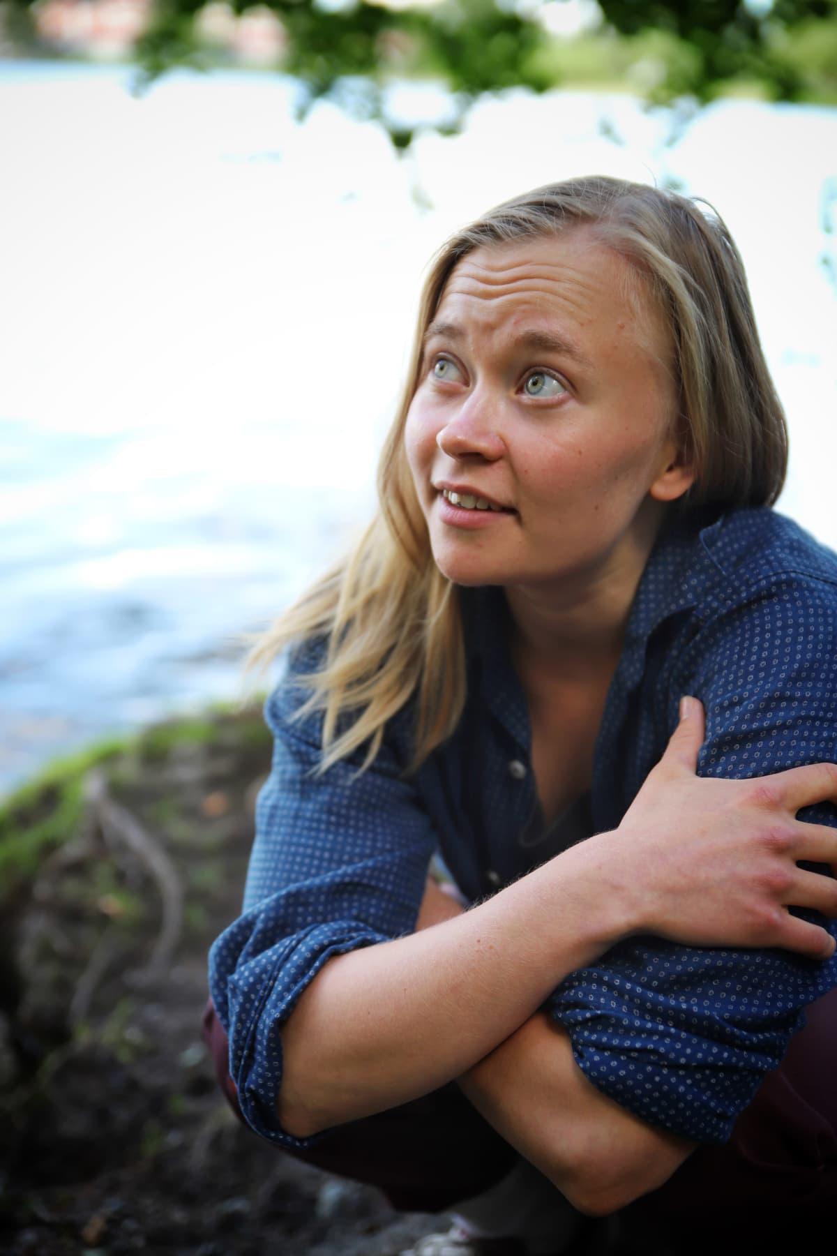 Eeva Rajakangas katsoo taivaalle Tohloppi-järven rannalla.