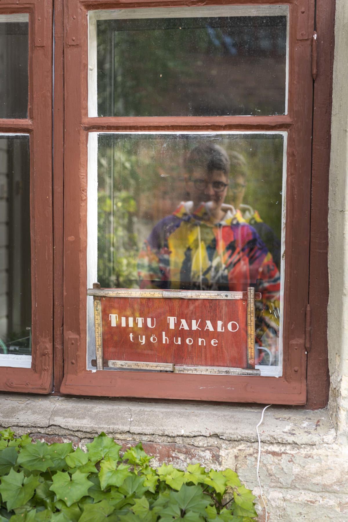 Sarjakuvataiteilija Tiitu Takalon kuva heijastuu hänen työhuoneensa ikkunasta.