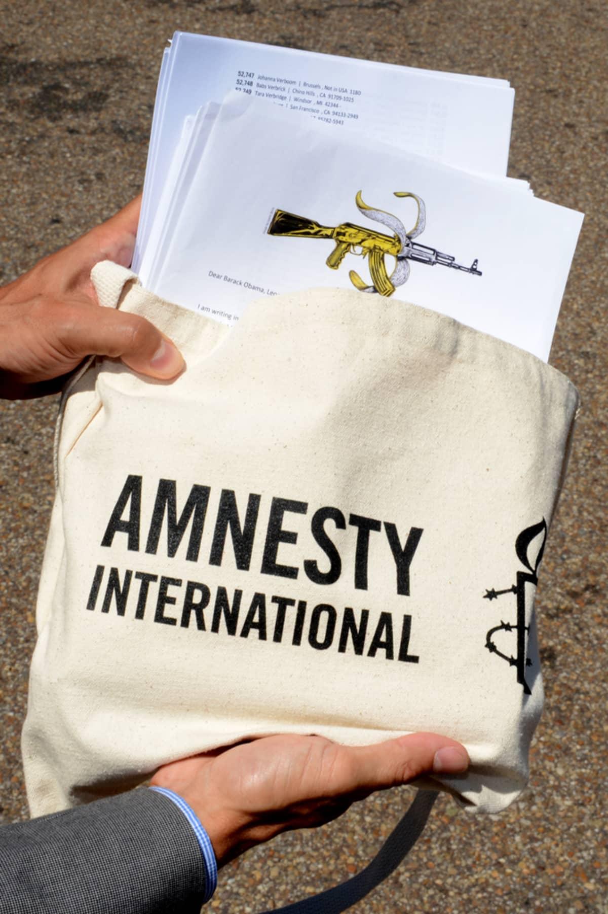 """Rauhanjärjestöt ympäri maailmaa toivovat asekauppasopimuksen etenevän - Amnesty International keräsi 60 000 nimen vetoomuksen, jossa vaaditaan estettäviksi """"sellaiset asesiirrot, jotka todennäköisesti johtavat vakaviin ihmisoikeusloukkauksiin, sotarikoksiin tai köyhyyteen."""" (Amnesty International)."""