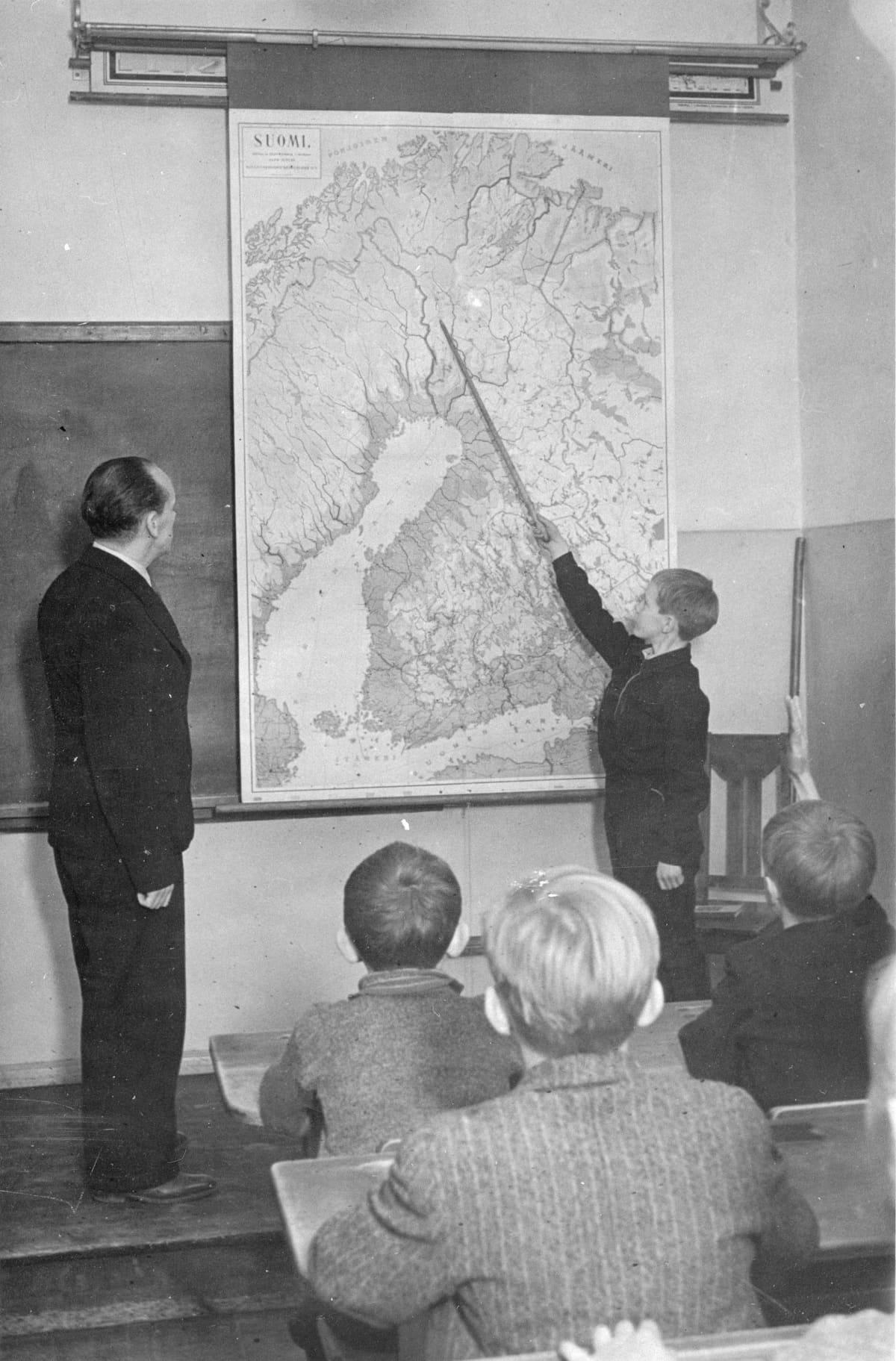 Poika näyttää karttakepillä kohtaa kartassa. Vanha mustavalkokuva.