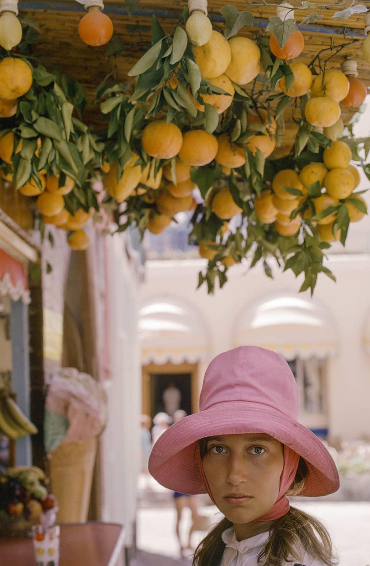 Anja with oranges. Lierihattuinen tyttö appelsiininoksan alla.