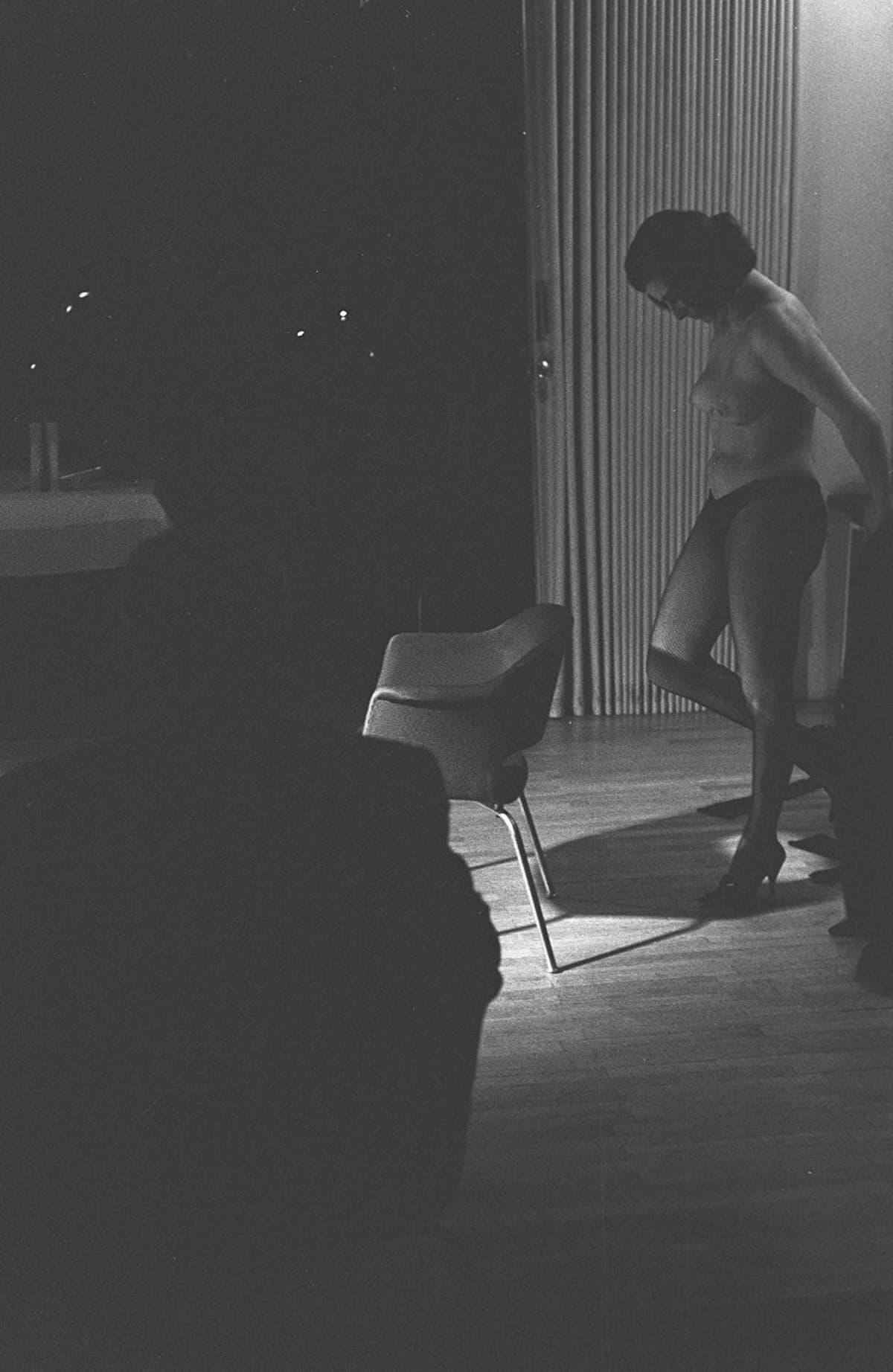 Nainen riisuuntuu ravintolan kabinetissa, mahdollisesti yksityinen striptease-esitys (strippari).