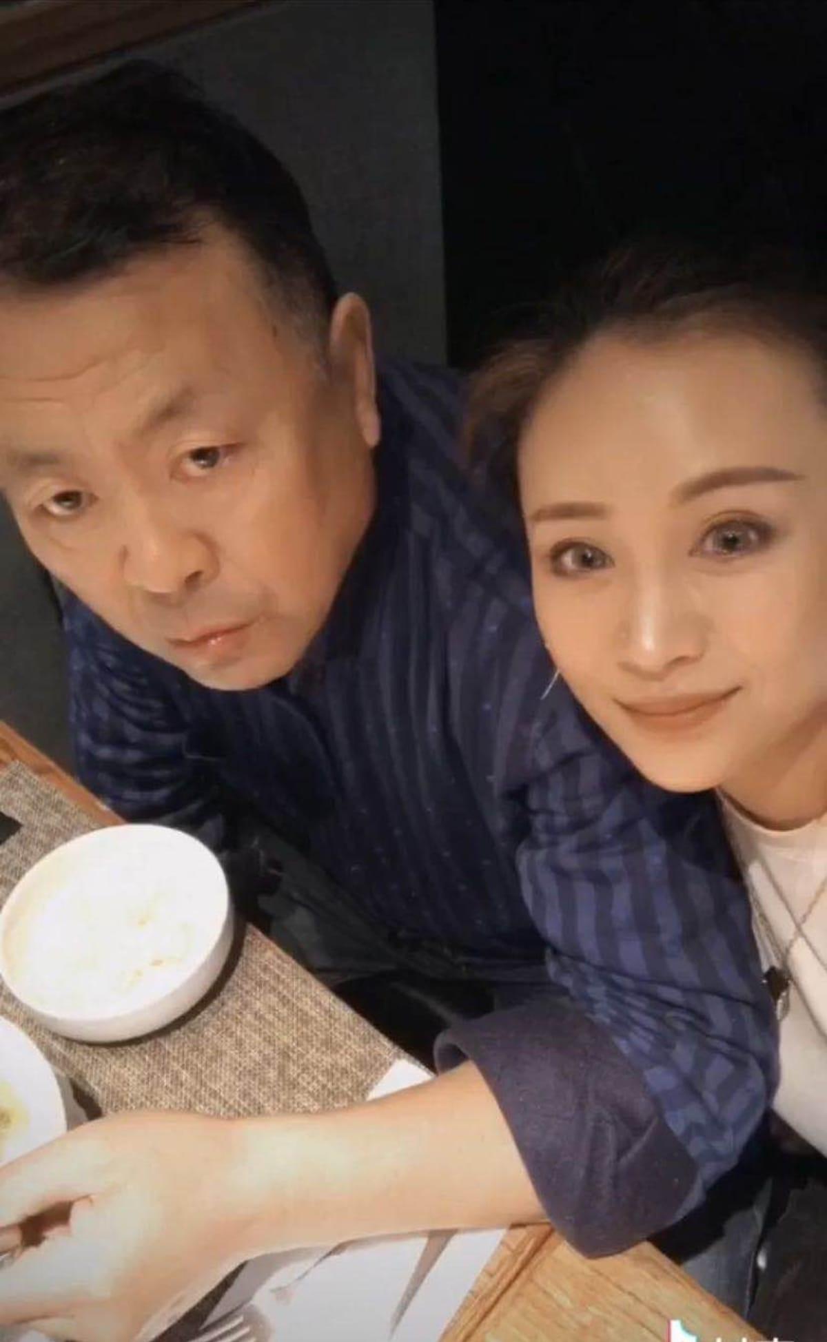 kiinalainen isä ja tytär katsovat kameraan pöydän ääressä