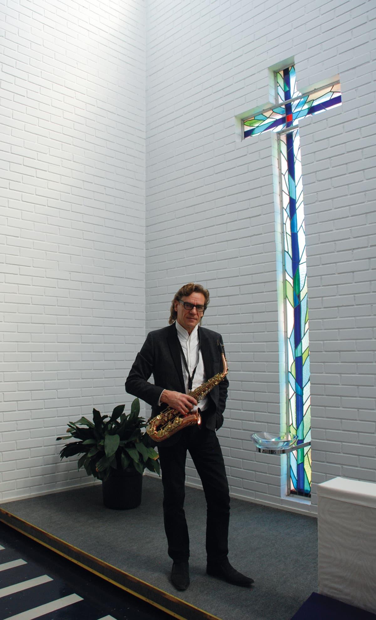Tuomas Hoikkala seisoo kirkon alttarilla puhallinsoittimen kanssa.