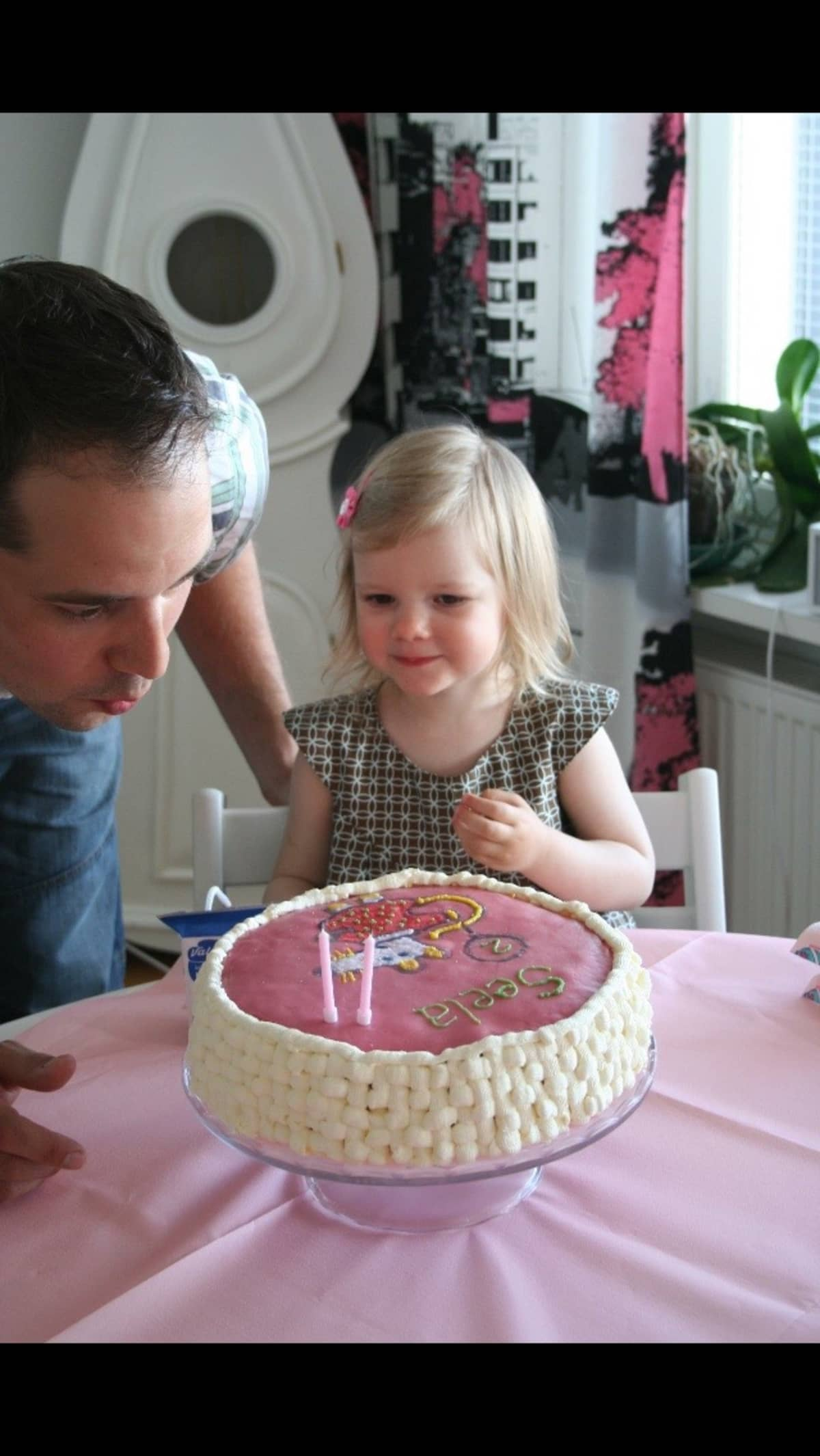 Isä ja tytär puhaltavat kynttilöitä syntymäpäiväkakusta.