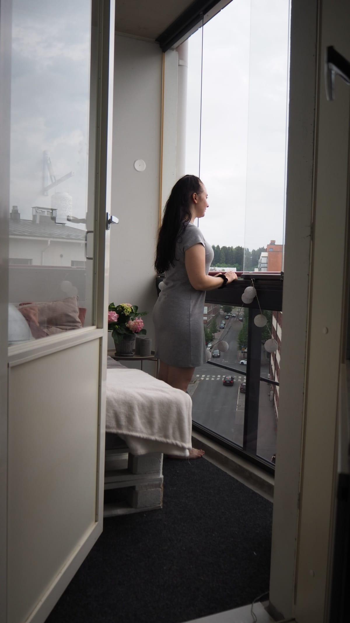 Henna-Riikka Niutanen katsoo kotinsa parvekkeella ulos kadulle.