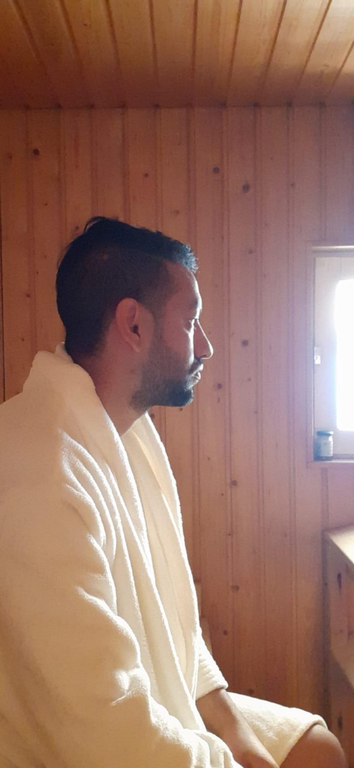 Pawan Aryal istuu saunatakki päällä saunassa.