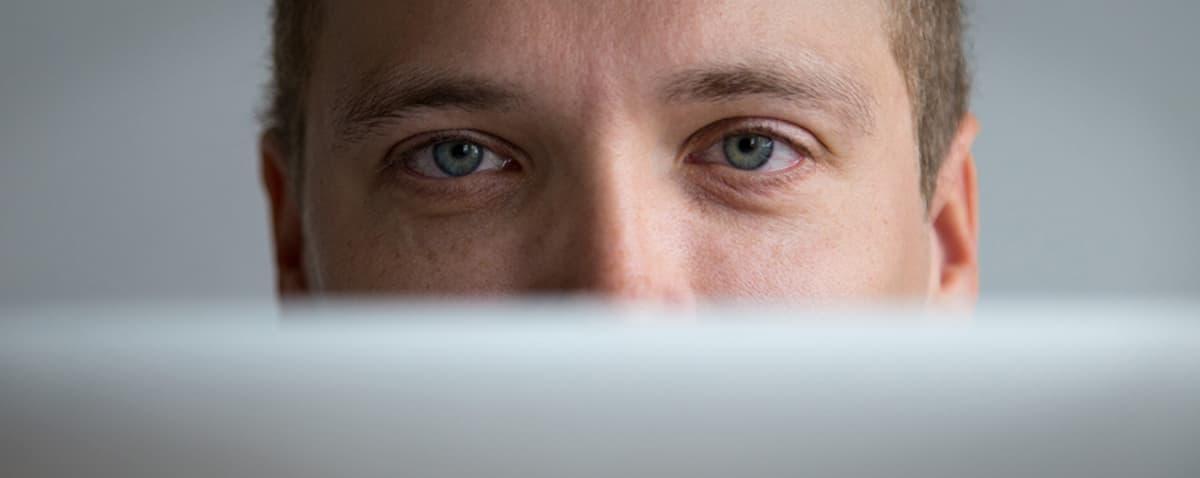 Henkilön silmät tietokoneen ruudun takana.