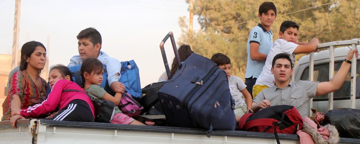 Kurdiperheet pakenevat Ras al-Ainin kaupungista torstaina.