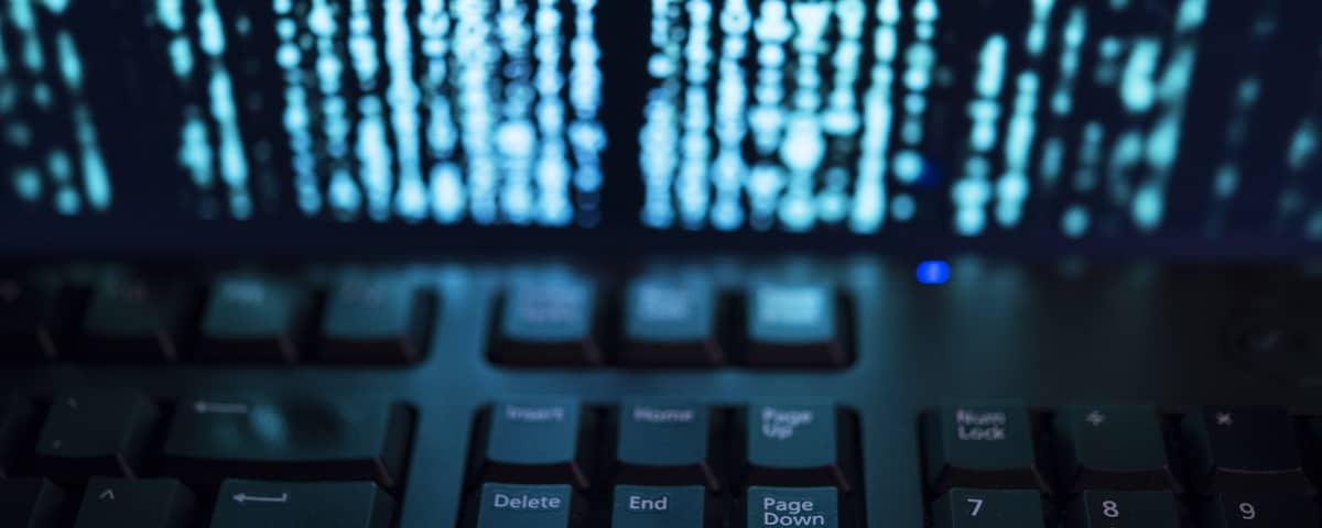 Tietokoneen näppäimistö ja tekstiä ruudulla