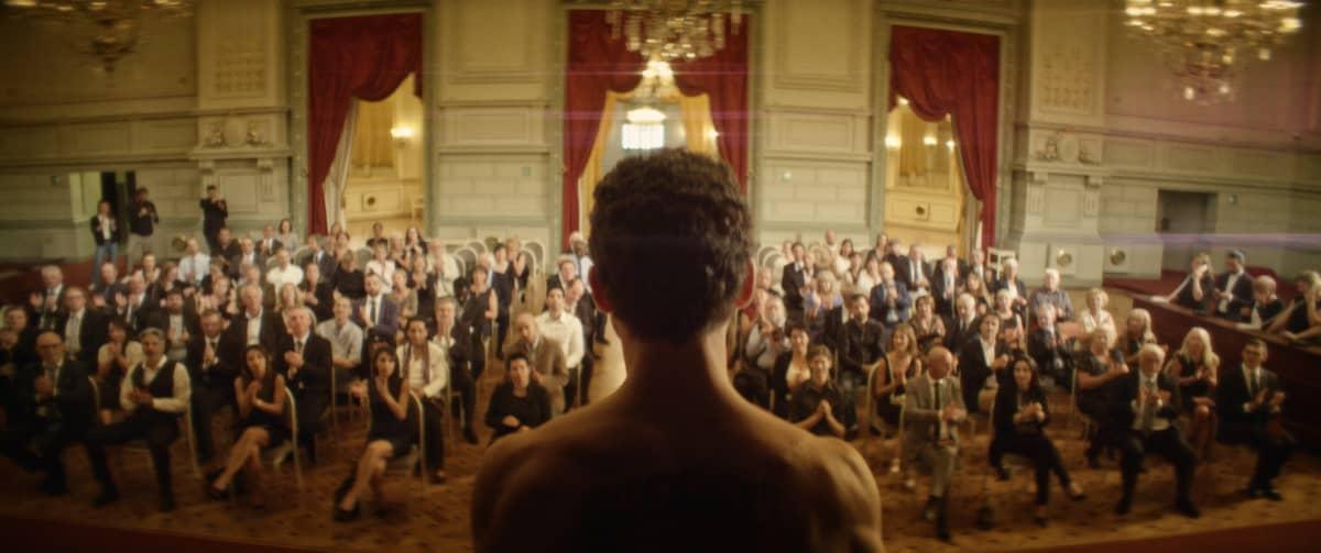 Mies teatterin näyttämöllä selin kameraan, katsomossa yleisöä.