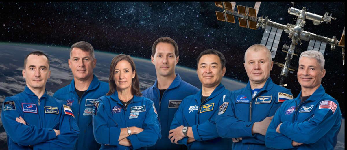 Seitsemän ihmistä avaruslentäjän haalareissa, käsivarret ristissä. Taustalla kuva ISS:stä Maan yllä.