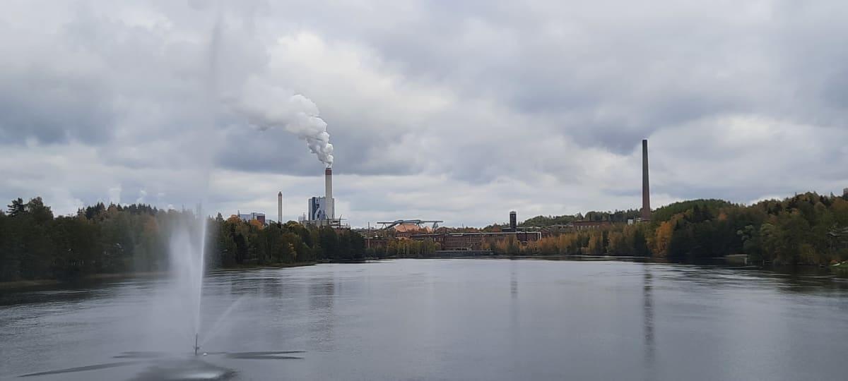 Kymijoki virtaa. Taustalla UPM:n sellutehdas ja Kymintehdas. Kuvan etualalla suihkulähde joessa