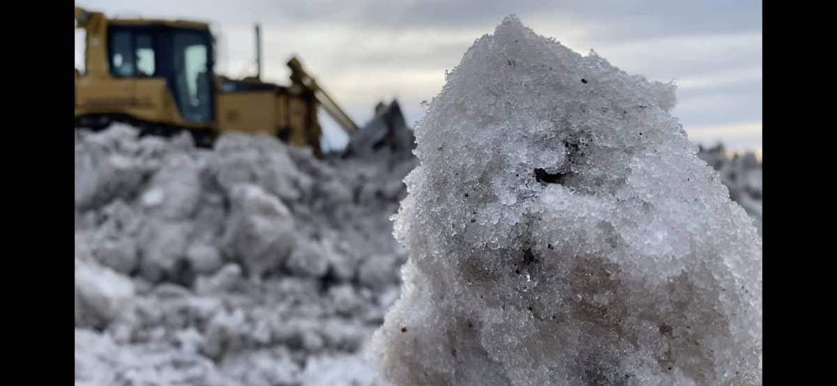 Puskutraktori tasaa lunta lumenkaatopaikalla