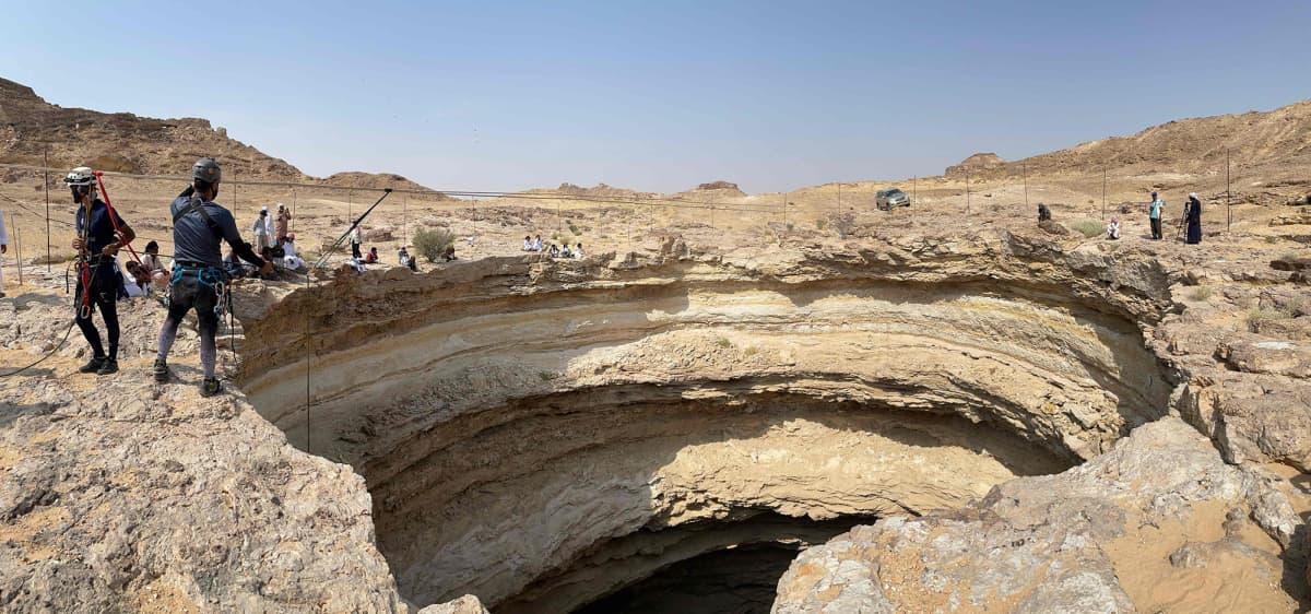 """Luolatutkijoita 100 metriä syvän """"helvetinkuilun"""" yläpuolella autiomaassa Jemenissä."""
