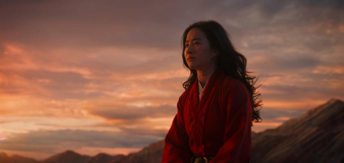 Närbild på Mulan (Yifei Liu) sitter på ett berg i solnedgången.