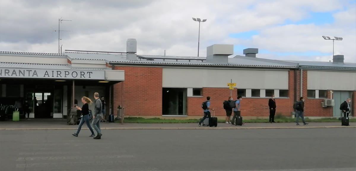 Lappeenrannan lentokentän edustalla odottelee matkustajia jatkokyytejä maskit kasvoillaan