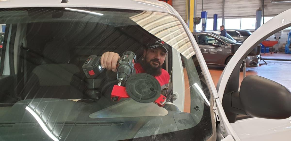Hameed Shinwari työväline kädessä autossa.