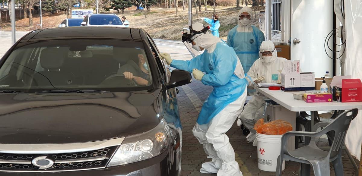 Terveydenhuollon työntekijä ottaa koronavirustestiä autonsa ikkunan avanneelta henkilöltä Cheonanissa Etelä-Koreassa 29. helmikuuta 2020.