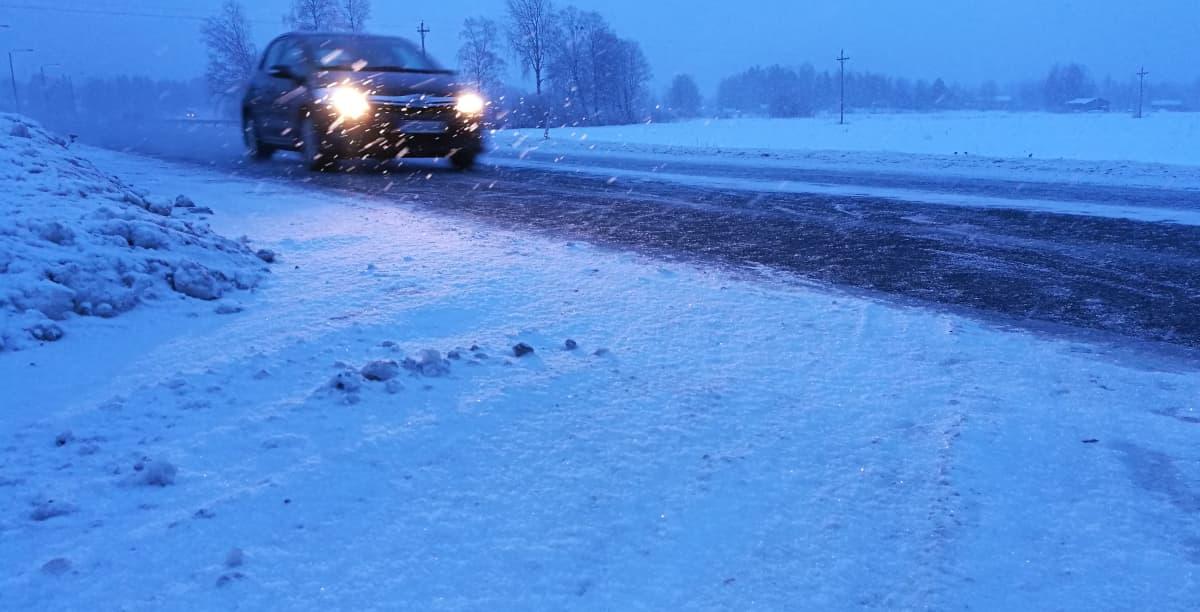 Kuvassa auto räntäsateessa maantiellä.