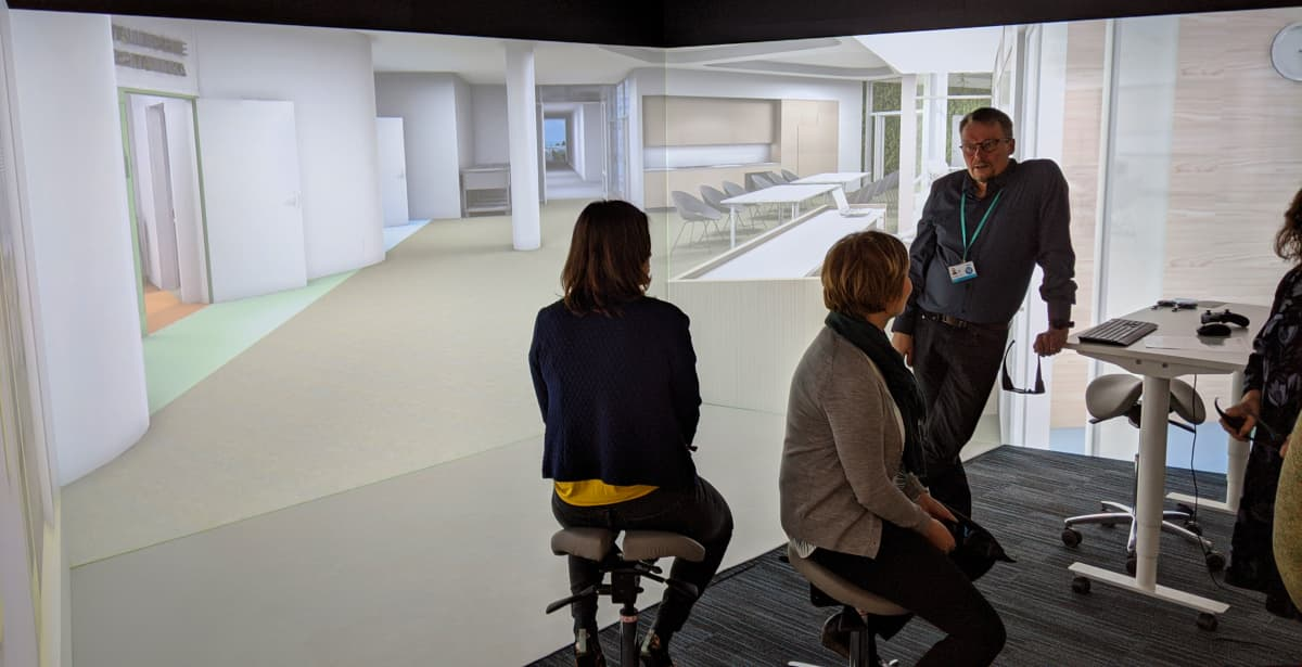 Joukko ylilääkäreitä ja ylihoitaja ovat tutustumassa suunnitteilla olevaan, uuteen Laakson yhteissairaalaan, 3D-huoneeseen projisoidun 3D-mallin avulla.
