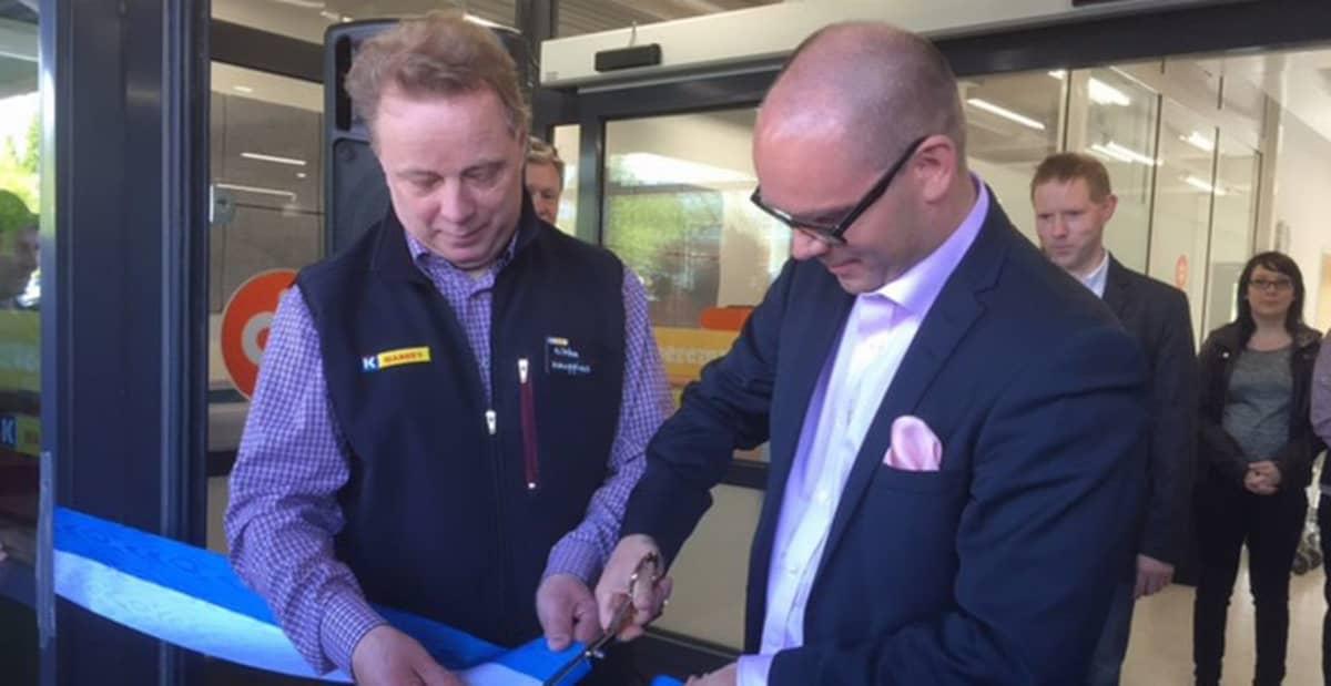Kaksi miestä leikkaa sinivalkoista nauhaa