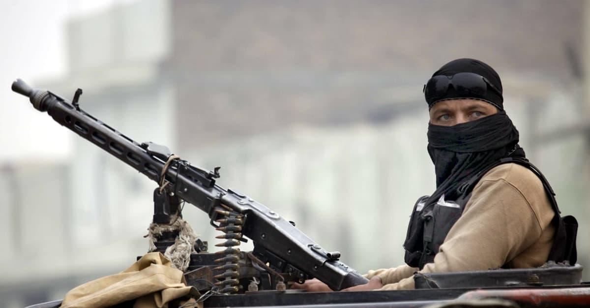 Kasvonsa peittänyt sotilas istuu konepistoolin takana.