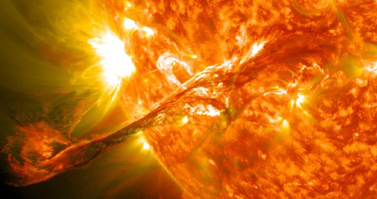 Oranssinpunaisena leimuavasta Auringosta syöksähtävä  purkaus.