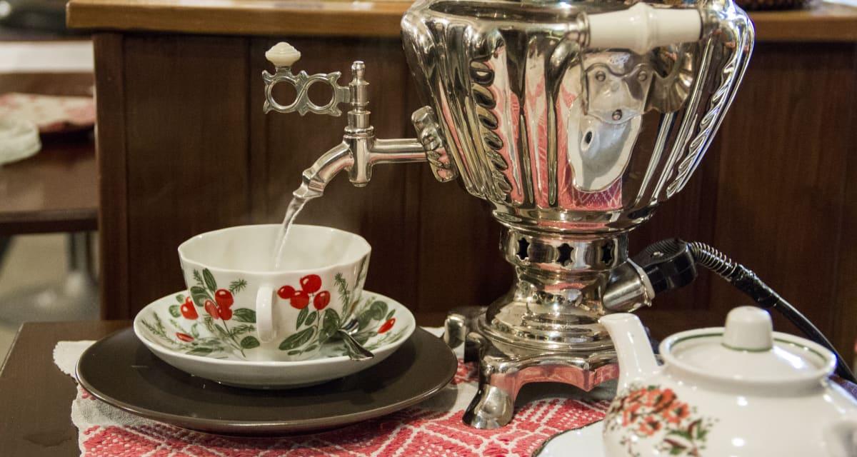 Samovaarista valuu kuumaa vettä venäläiseen teekuppiin.